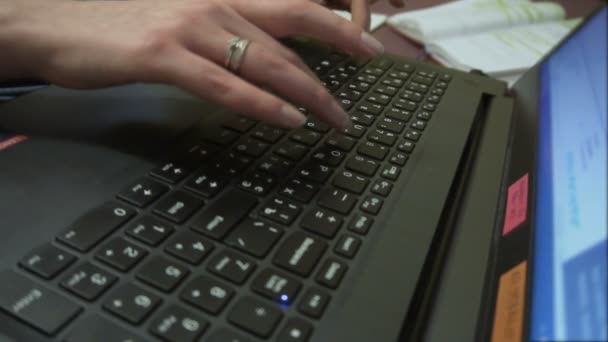 Womans hands pressing keys on a laptop keyboard