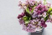 Un bouquet di fiori di lillà su uno sfondo grigio cemento.