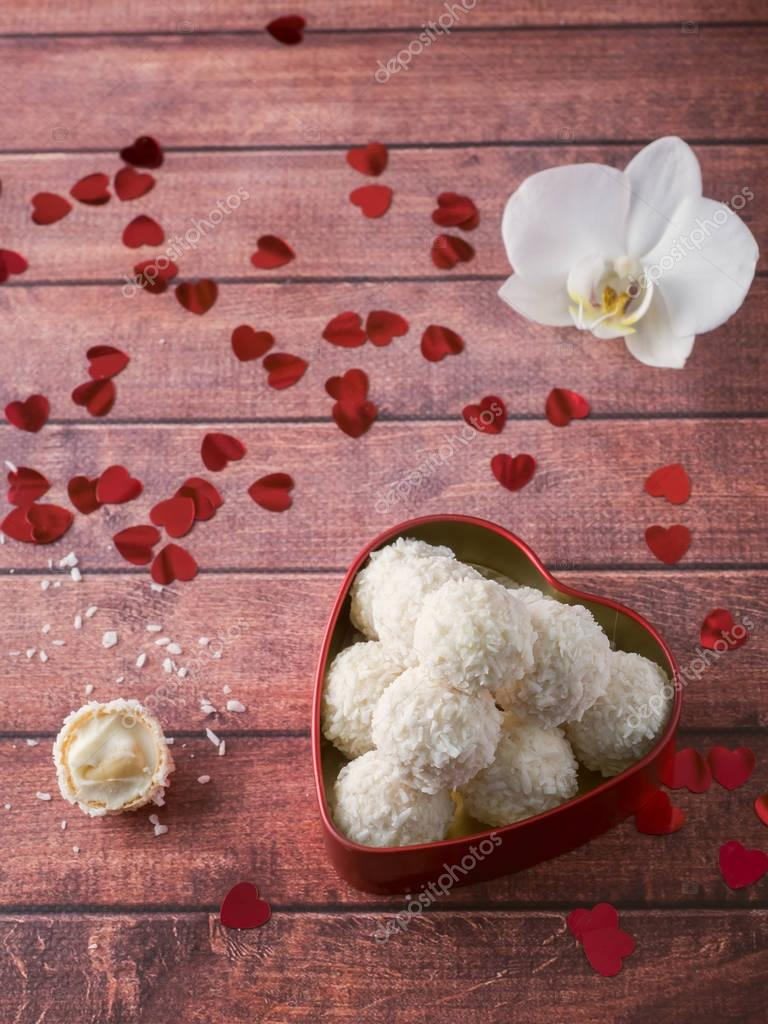 Coconut candy in a red heart Orchid Flower Wooden Background Copy space