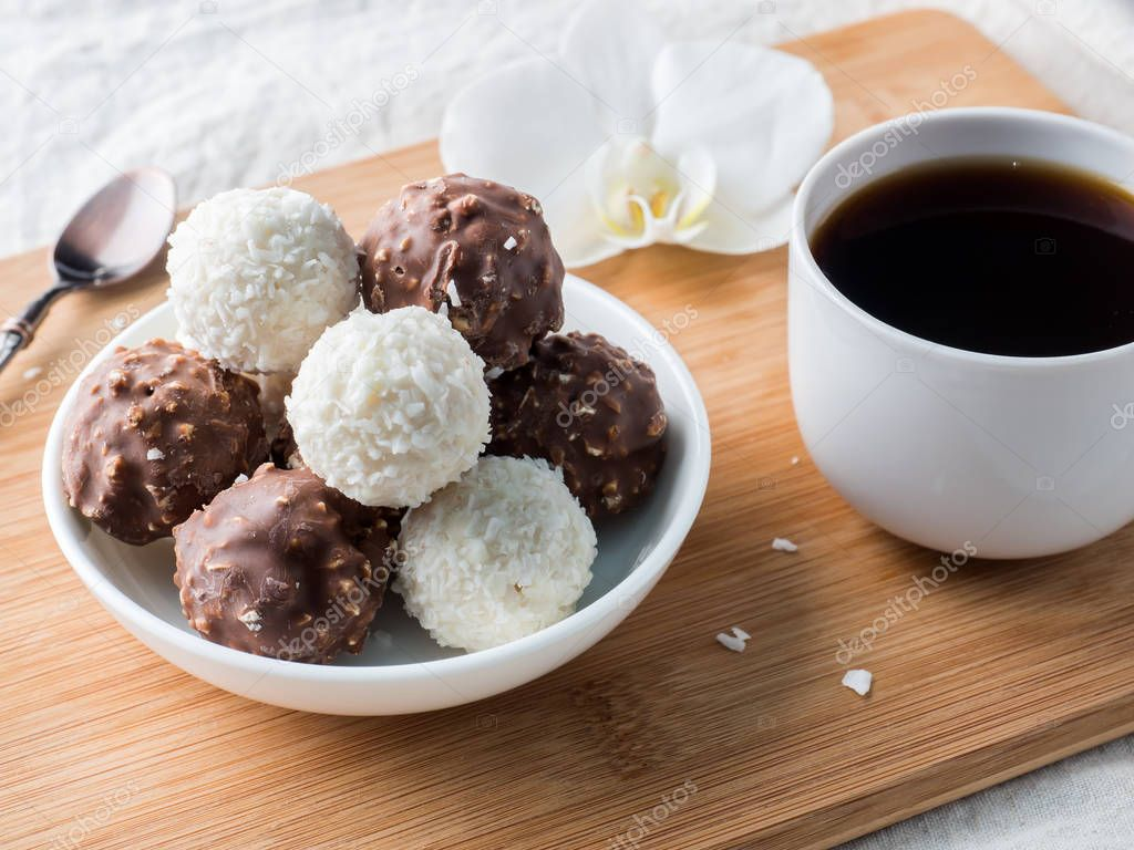 Chocolate and Coconut Candies in a Bowl on a Wooden tray Coffee Cup Orchid.