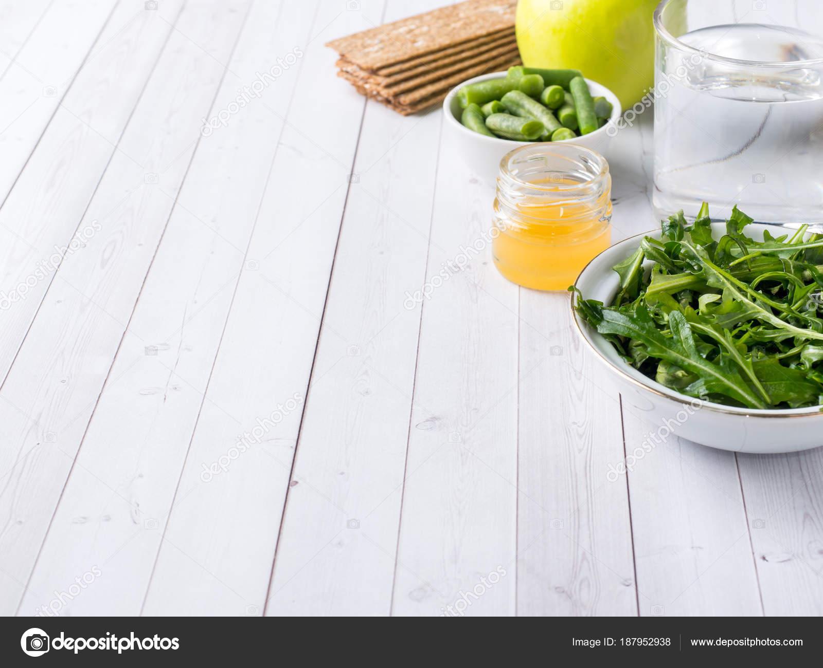 Здоровая диета еда на столе рукколой зеленая фасоль apple воды мед.