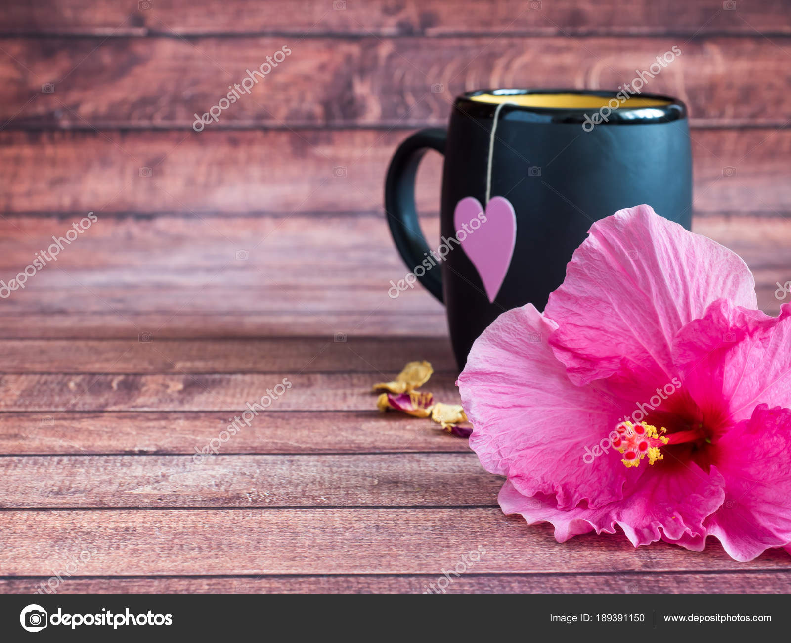 Black mug of tea with a pink heart on a string pink hibiscus flower black mug of tea with a pink heart on a string pink hibiscus flower on dark izmirmasajfo