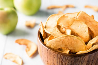 Dried apples in a wooden bowl Ripe green apples on the table