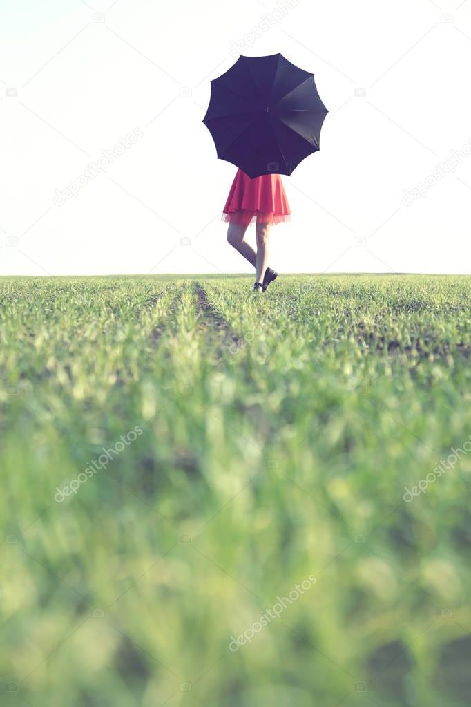 woman hides behind a black umbrella on a spring day on a green grass