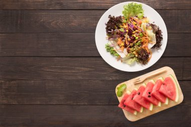 Fresh salad and watermelon on the wooden background. Top view