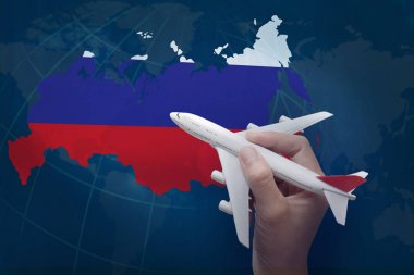 hand holding airplane with map of Russia.