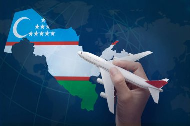 hand holding airplane with map of Uzbekistan.