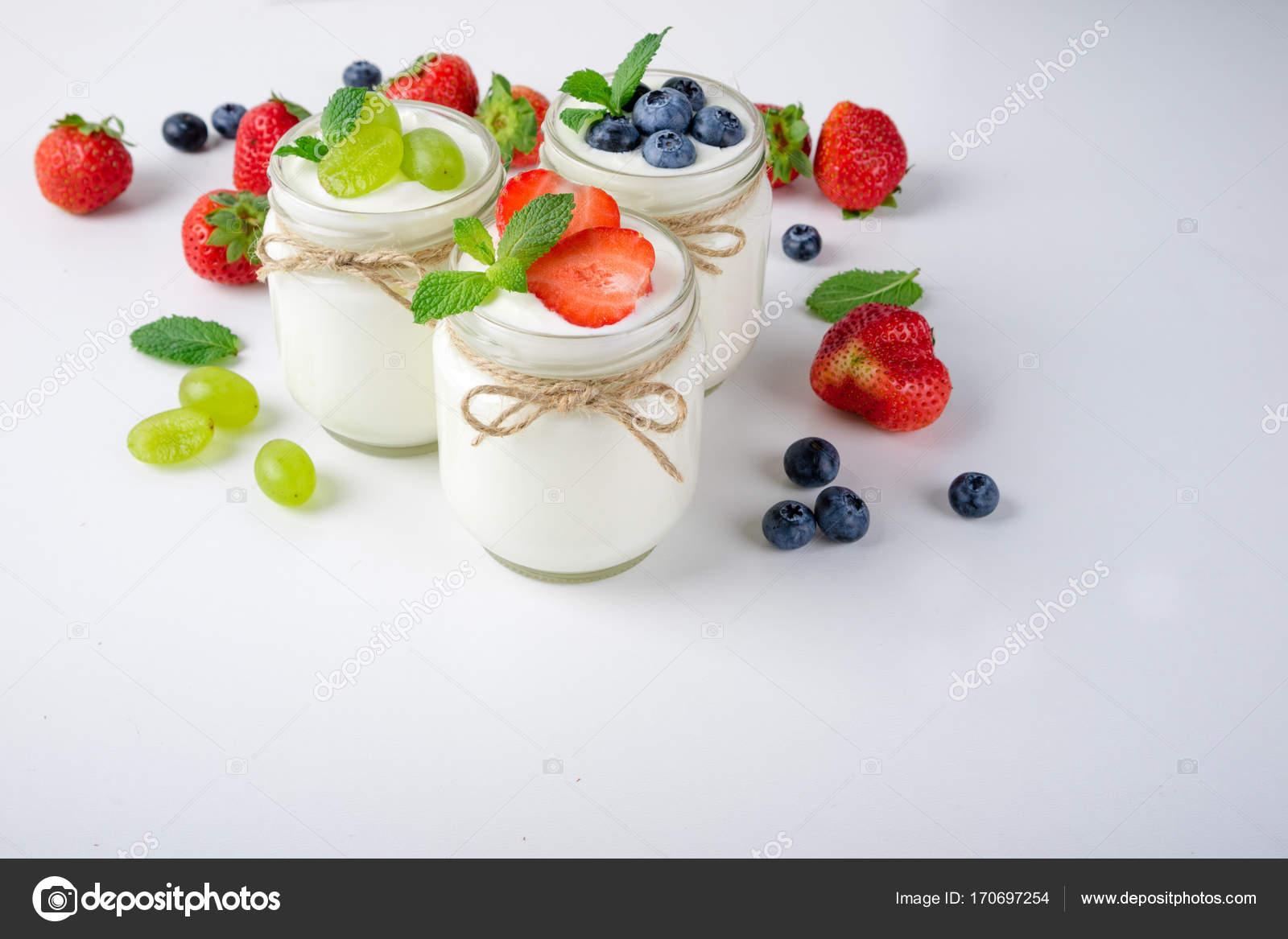 Свежий йогурт с ягодами в стеклянных банках. Здоровое питание.
