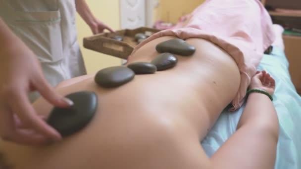 Massage-Master stellt auf der Rückseite der eine junge Frau heißen Steinen