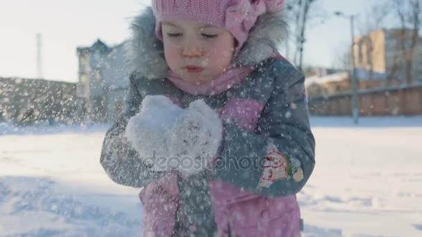Malá holka fouká ruce sníh s matkou