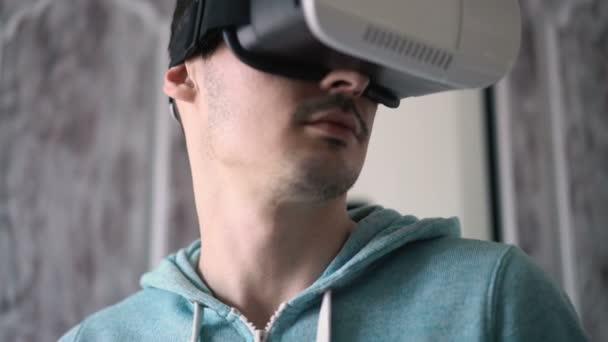 Mann trägt Virtual-Reality-Headset im Wohnzimmer.