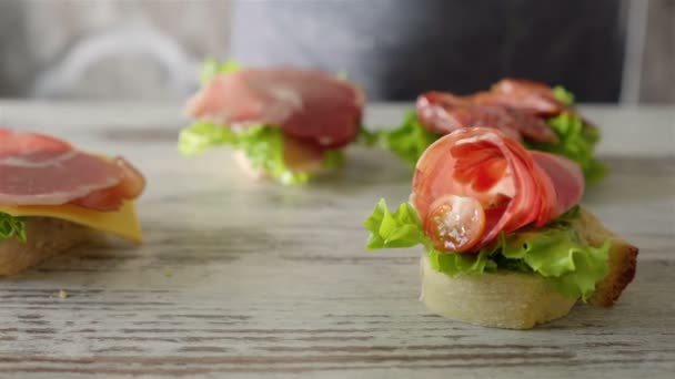 Woman making sandwich with salad leaf, spread, cherry tomatoes