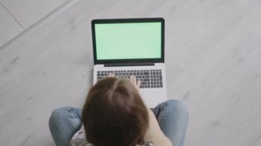 Young woman sitting at the laptop close-up