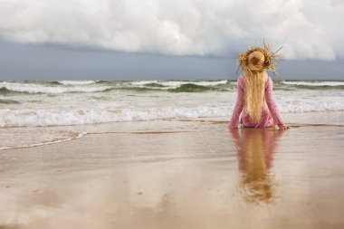 Blond woman sitting on sea shore