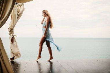 Young female walking on beach resort
