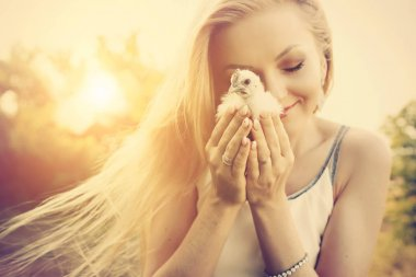 woman holding little white chicken