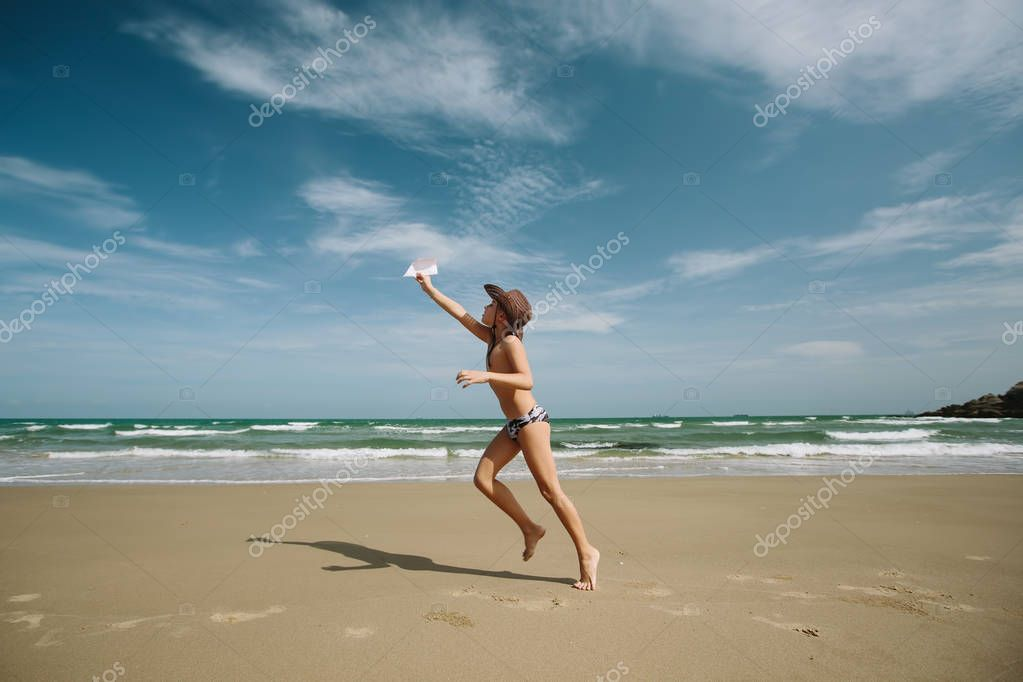 Young Boy throwing paper plane on beach
