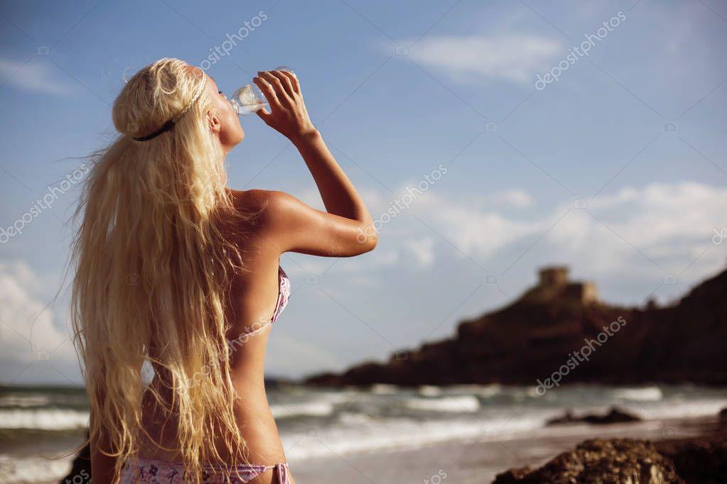 blond woman in swimsuit drinking water