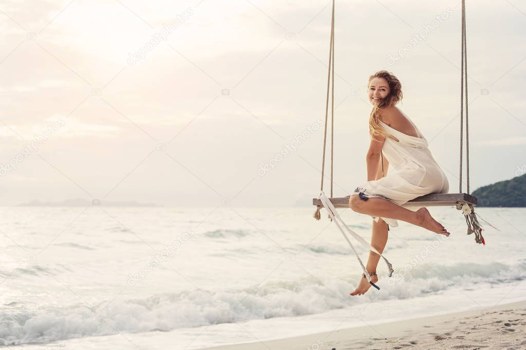 Happy girl on swing on tropical sea shore