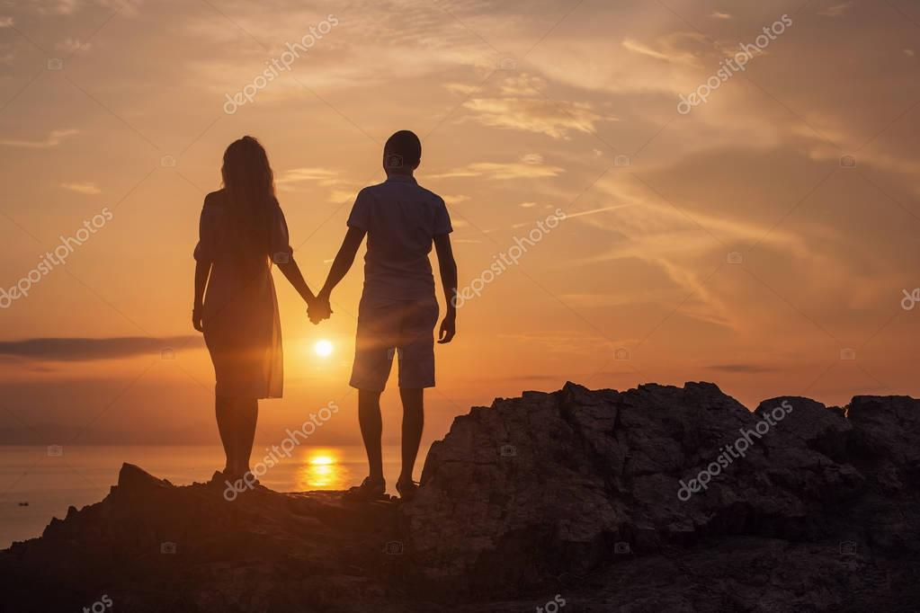 Silhouette of Love couple standing on  cliff