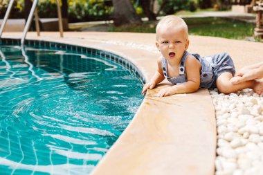 baby boy near swimming pool
