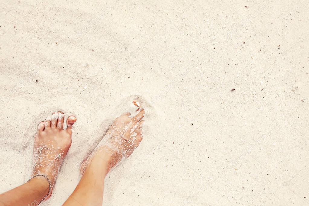 Female feet in white beach sand