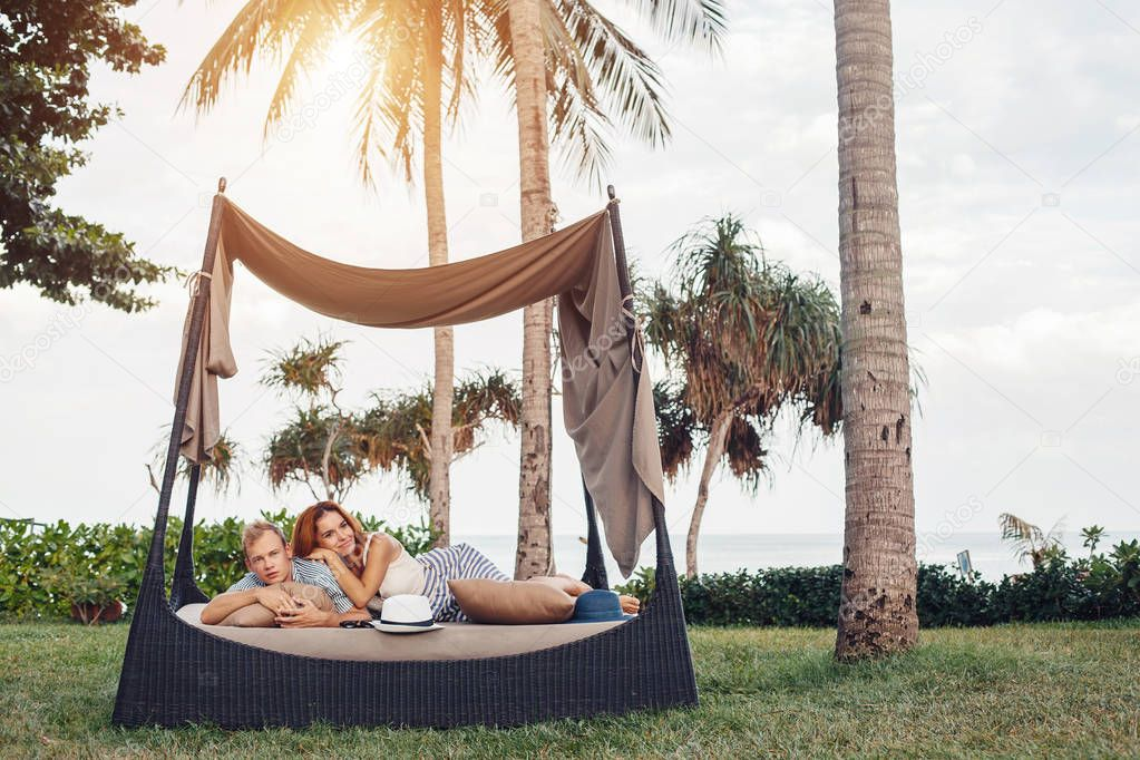 Young couple lying under palm trees