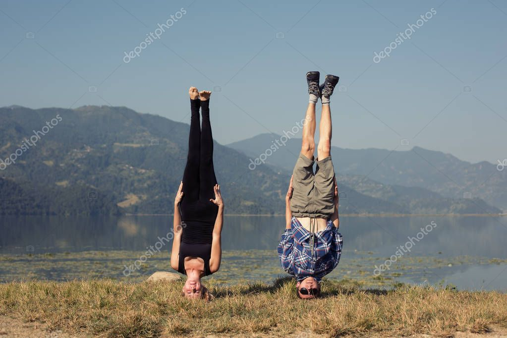 Couple of young yogis stand on head