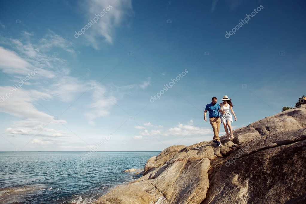 Man and woman walking on beautiful sea shore