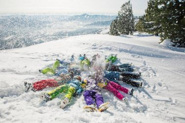 People lying on a snowy mountain top
