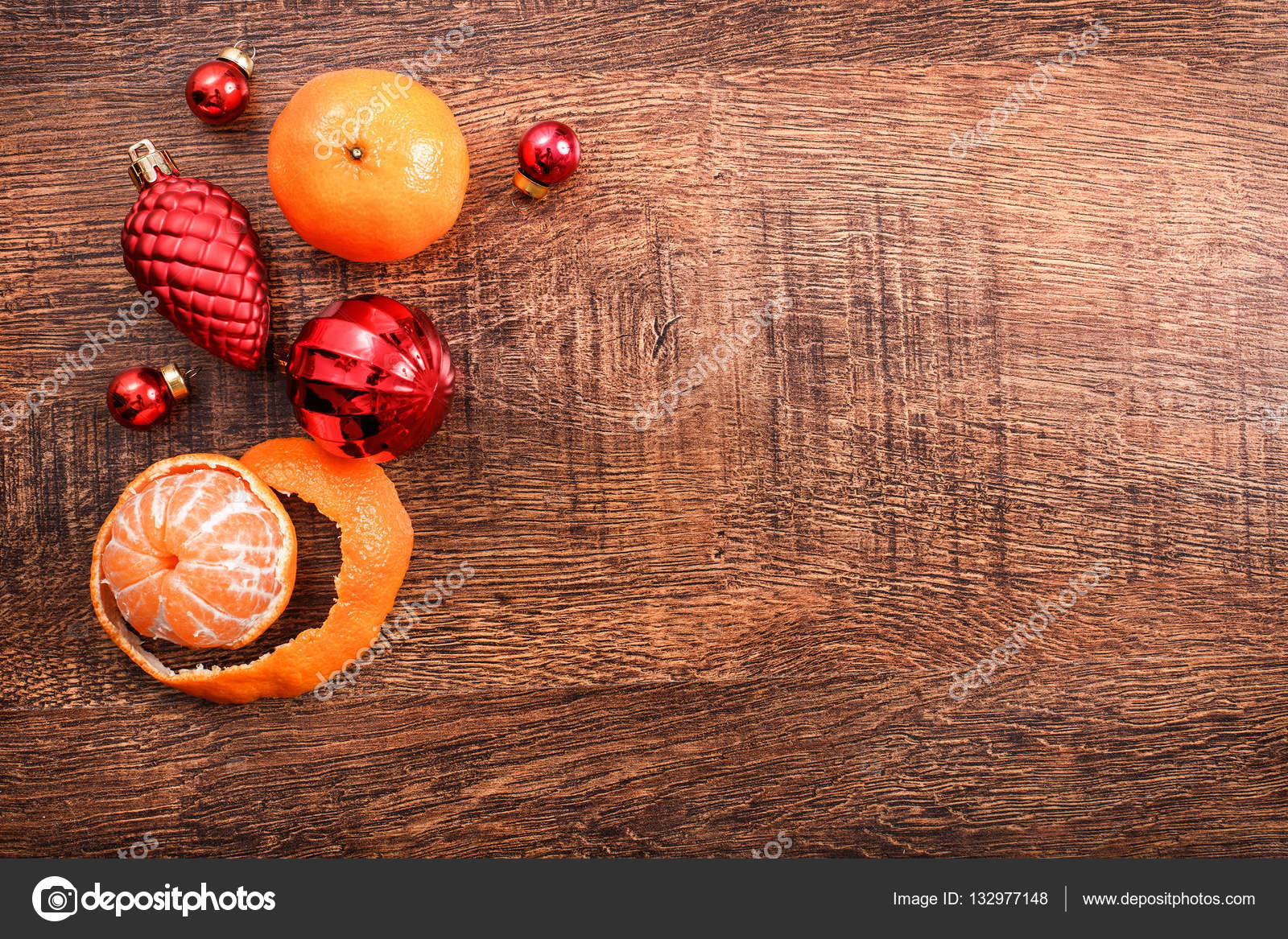 Red Christmas ornaments, food decor and fir tree branch on a rustic wooden background.
