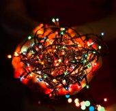 Ženské ruce držící vícebarevné vánoční světelné dekorace na pozadí tmavě holiday. Téma Vánoce a nový rok. Tónování