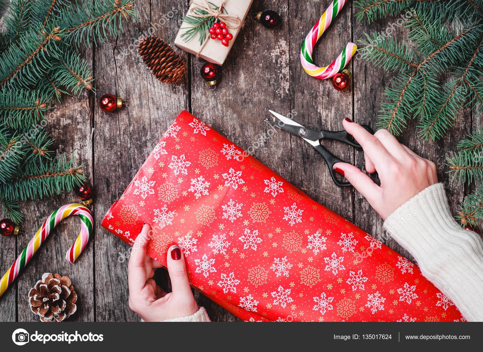 Weibliche Hand umschließt Weihnachtsgeschenk auf Urlaub Verpackung ...