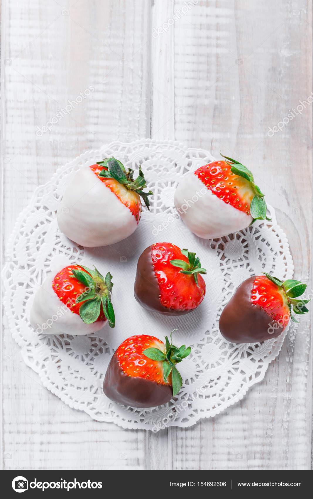 Fresh Strawberries Dipped In Dark And White Chocolate On Light