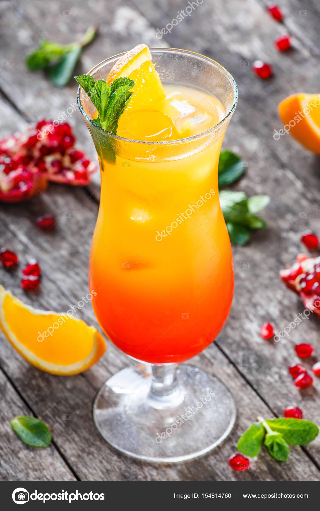 Tequila sunrise cocktail with mint, orange and pomegranate ...