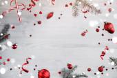 Veselé Vánoce a Nový rok pozadí. Vánoční vánoční přání z létajících dekorací, jedlových větví, červených kuliček, sněhových vloček, jisker, bokeh, světla na dřevěném pozadí. Selektivní zaměření
