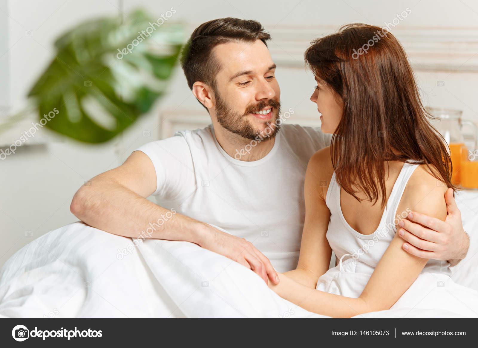Jong volwassen heteroseksuele koppel liggend op bed in de slaapkamer