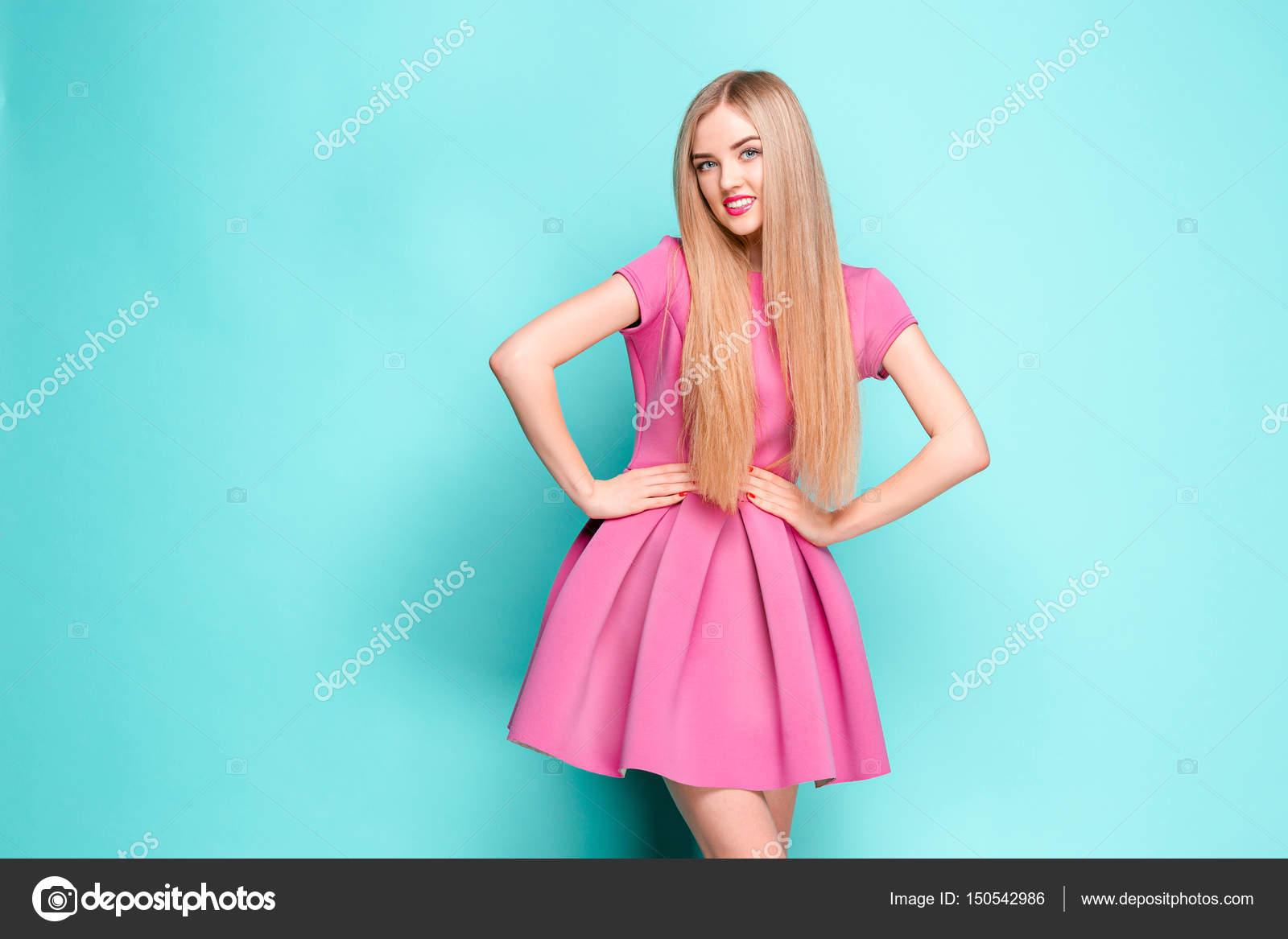 52f841ecab47 Usmívající se krásná mladá žena v Růžové mini šaty pózuje ve studiu — Stock  fotografie