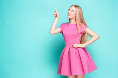 Smiling beautiful young woman in pink mini dress posing, presenting something and looking away. Three quarter length studio shot on blue background. stock vector