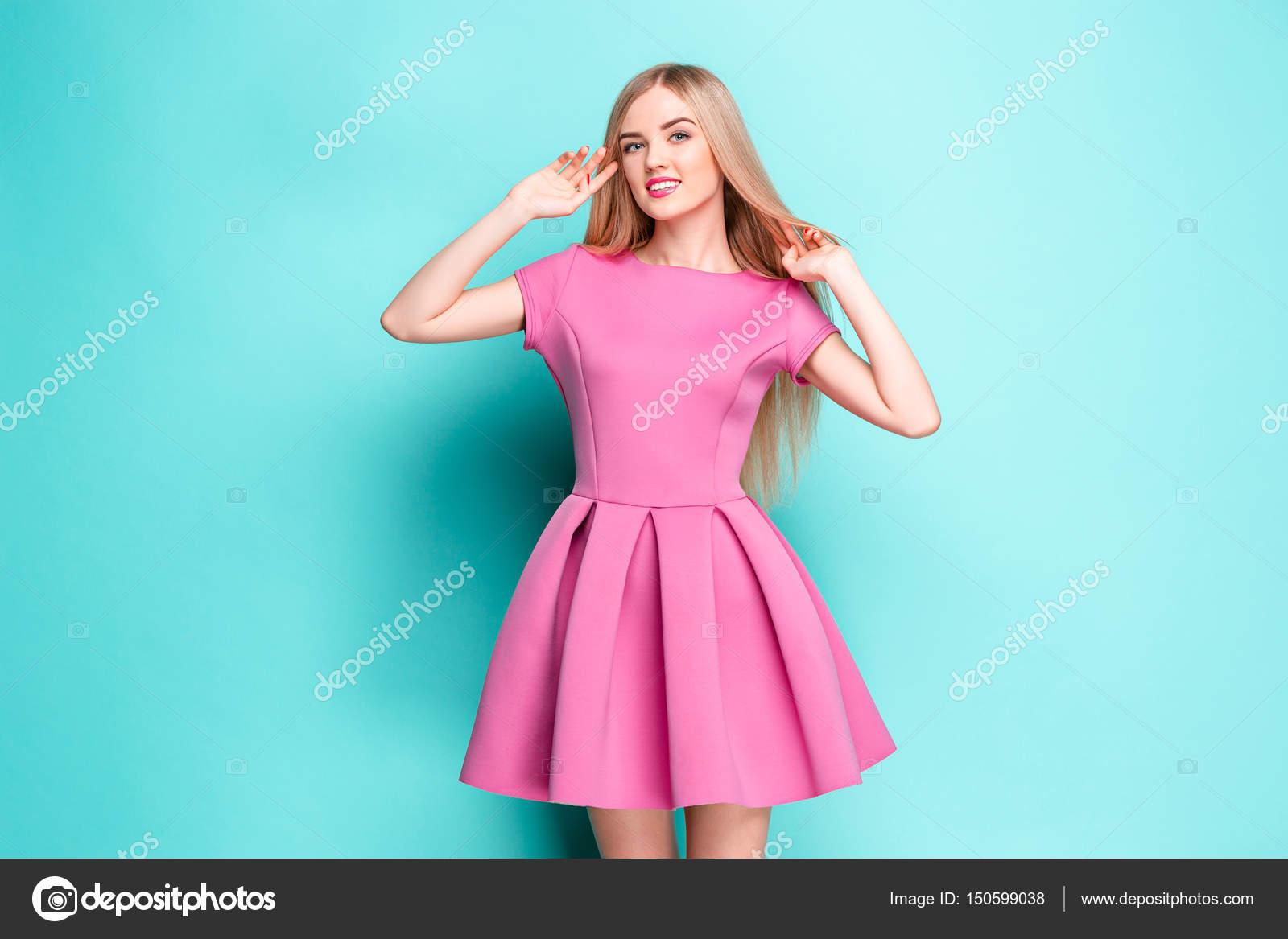 e1185bc11 Sonriente mujer joven hermosa en vestido mini rosa posando en el ...