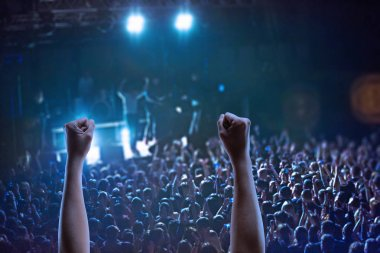 The silhouettes of concert crowd in front of bright stage lights
