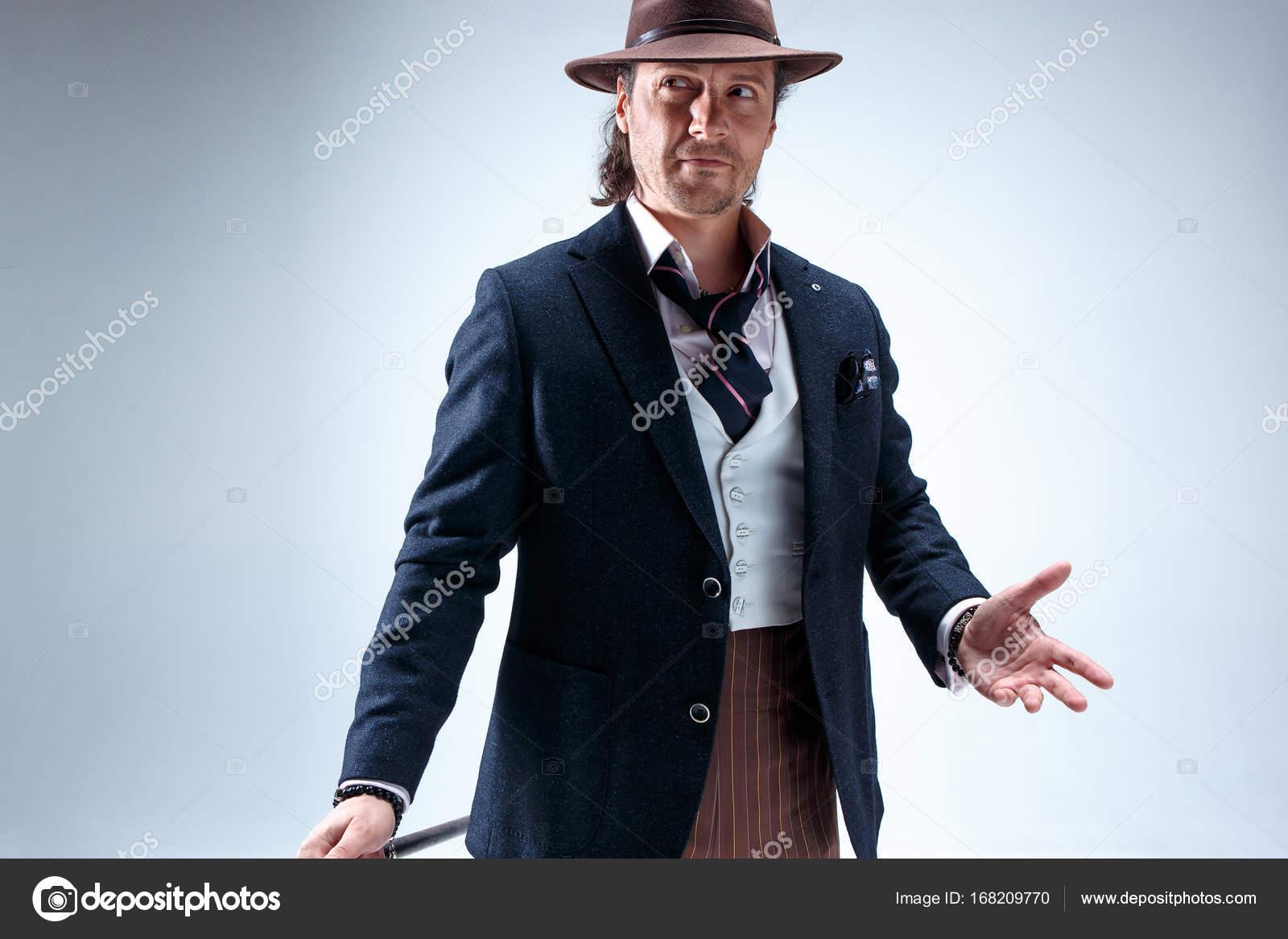 El maduro barbudo hombre en un traje y un sombrero con caña. Aislado en un  fondo de estudio gris — Foto de vova130555 gmail.com 0664d6fac89