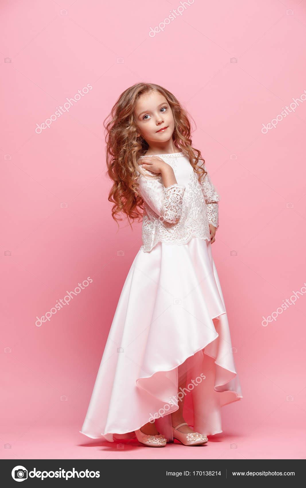 Longitud total de niña hermosa vestida de pie y posando sobre fondo ...