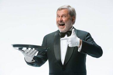 Senior waiter holding tray