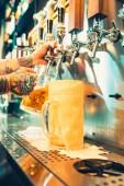 ruka barman lití velké pivo ležák v kohoutku.