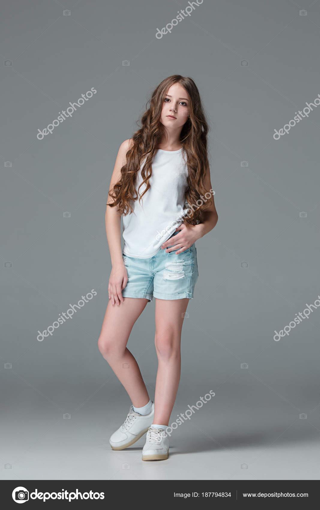 6028473d67e824 Tout au long de la jeune fille mince en short en Jean sur fond gris ...