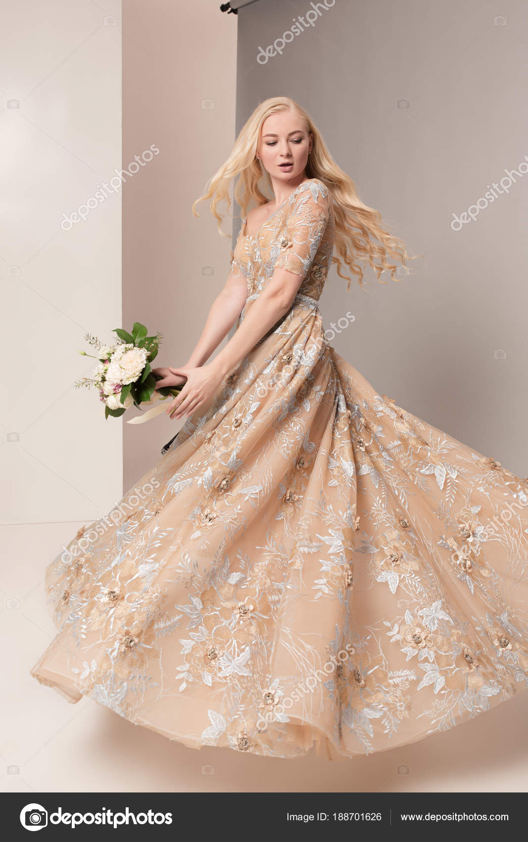 Ik Zoek Een Jurk Voor Een Bruiloft.Bruid In Mooie Jurk Permanent Binnenshuis In Witte Studio Interieur