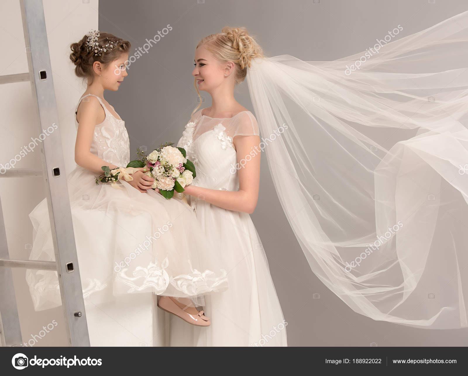 Niñas bonitas con flores vestidas con vestidos de novia — Foto de ...