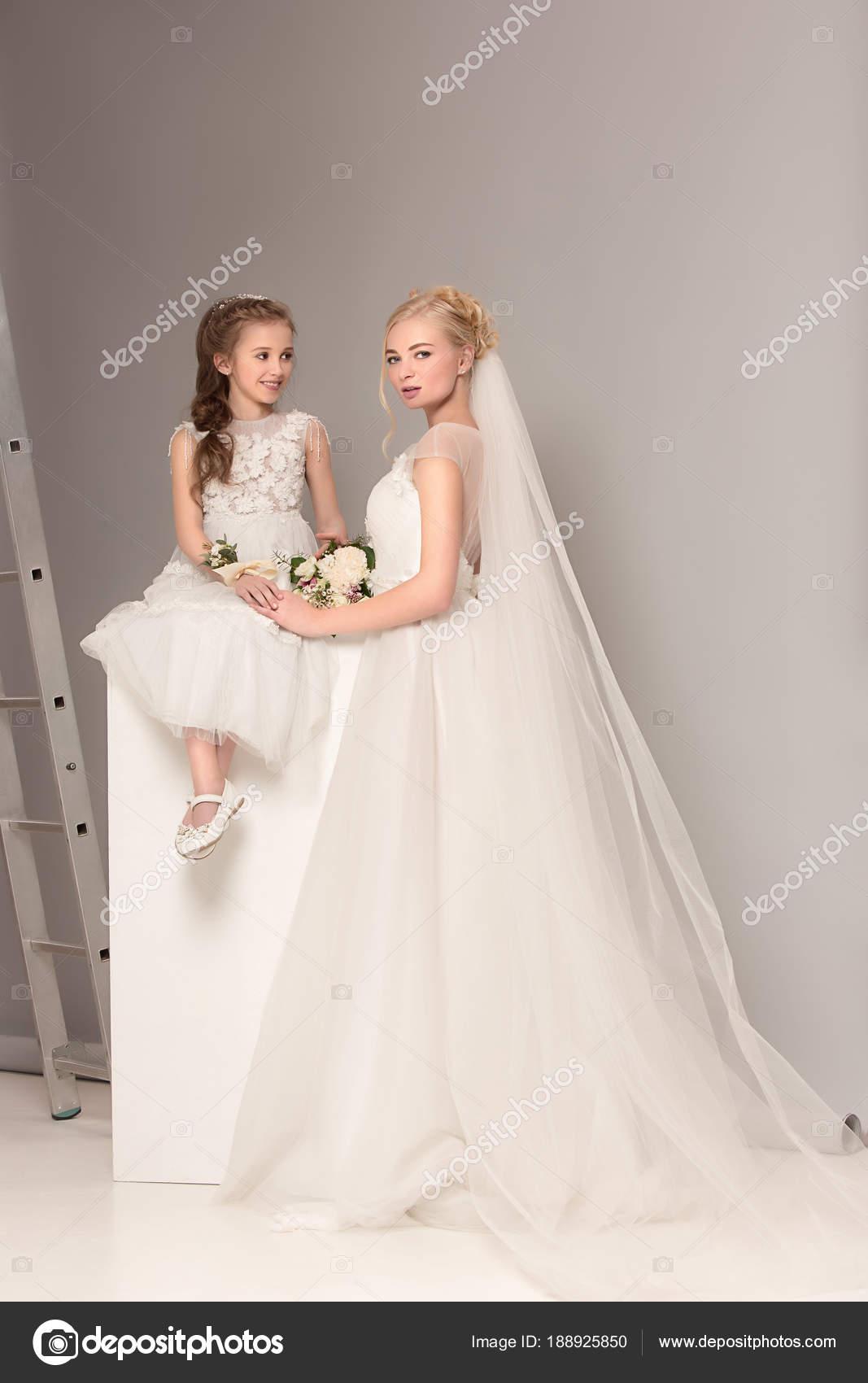 Hezká holčička s květinami a ženské nevěsta na sobě svatební šaty. Krásná  malá přítelkyně. holky sní o svatbě. Krása 4b13c7cece