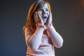 Fotografie das junge attraktive Teenie-Mädchen sieht überrascht isoliert auf dunkelblau aus